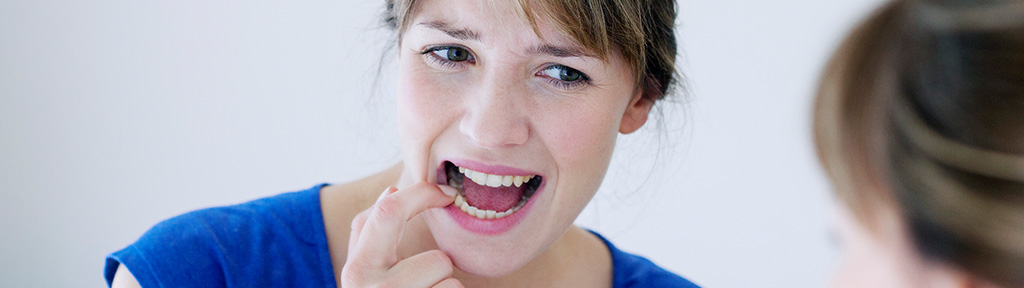 woman inspecting her teeth in the mirror wanting to prevent early gum disease