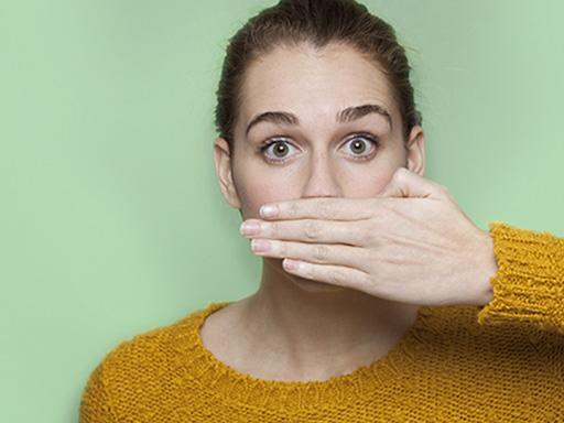 woman afraid of bad breath covering up mouth with her hand
