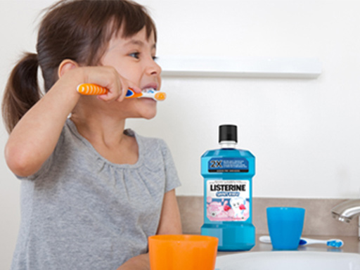 little girl brushing her teeth and using Listerine mouthwash