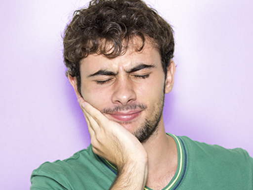 younger man holding cheek suffering from cavity pain